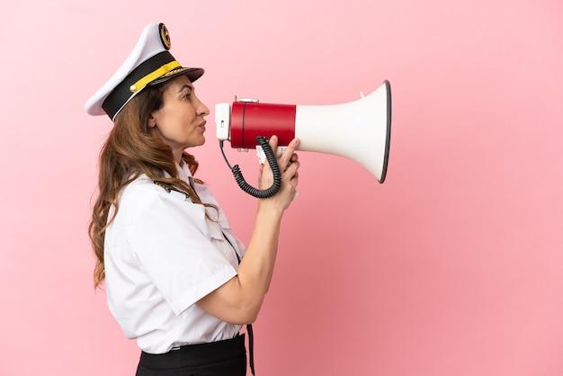 Женщина-пилот самолета средних лет изолирована на розовом фоне и кричит в мегафон