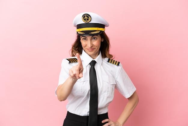 Женщина-пилот самолета средних лет изолирована на розовом фоне, показывая и поднимая палец