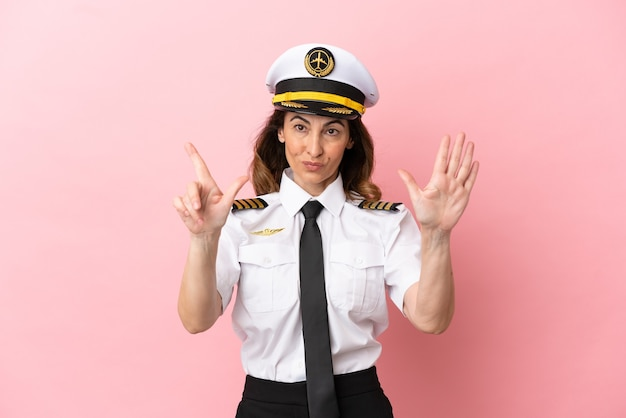 Airplane middle aged pilot woman isolated on pink background counting seven with fingers