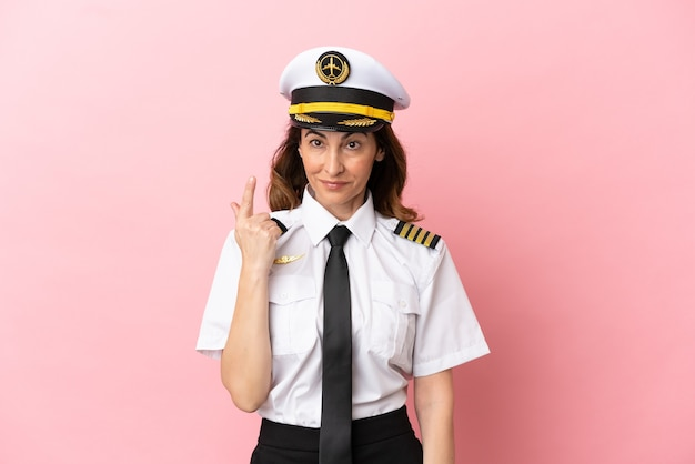 Airplane middle aged pilot woman isolated on pink background pointing with the index finger a great idea