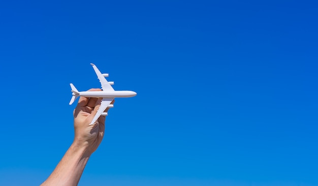 Airplane model in hand against clear blue sky