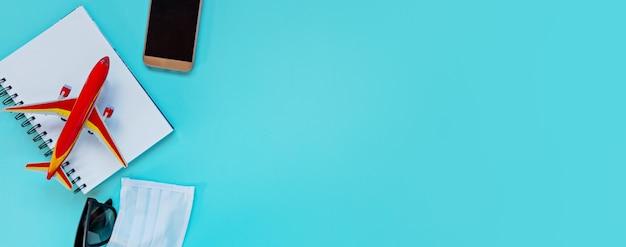 Модель самолета, ноутбук, телефон, медицинская маска и очки. отмена рейса из-за воздействия туристической концепции коронавируса covid-19. пространство для копирования баннеров flatlay