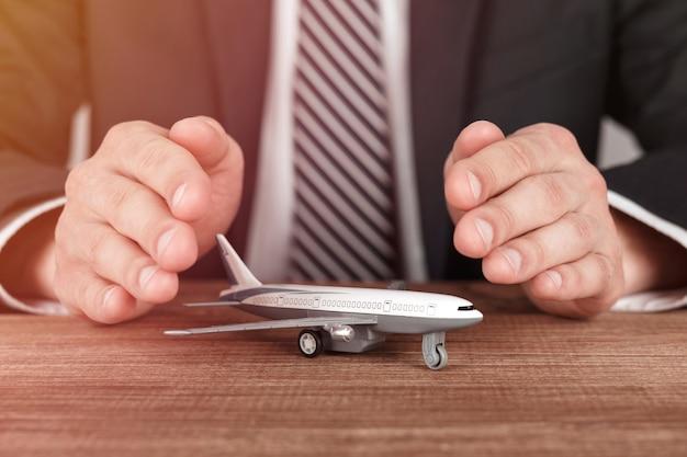 保護のジェスチャーで手に囲まれた飛行機モデル。航空会社の安全、セキュリティ、保険の概念。