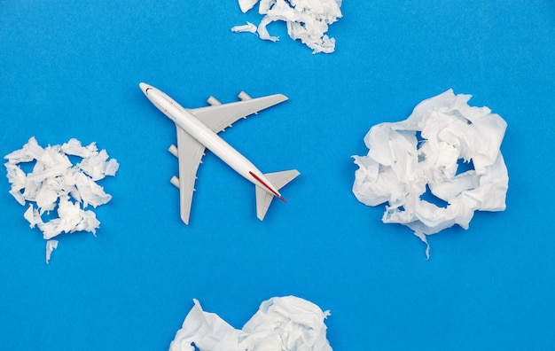 Airplane model with paper ball instead of white clouds on blue background