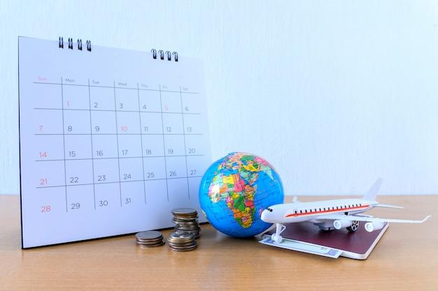 木製のテーブルに紙のカレンダーを持つ飛行機モデル。旅行の計画