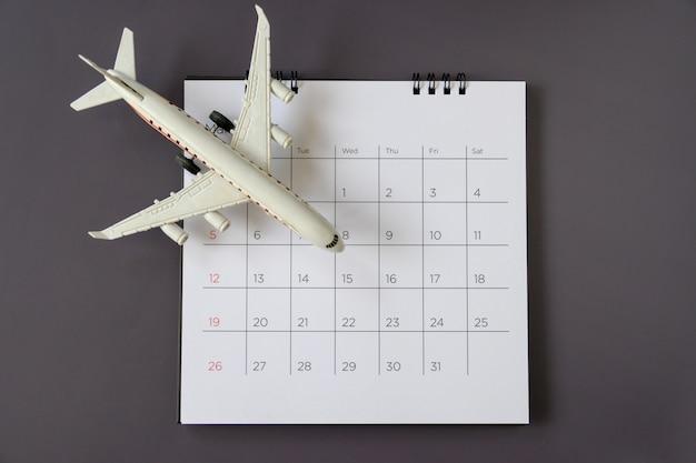 紙のカレンダー付きの飛行機モデル。旅行の計画
