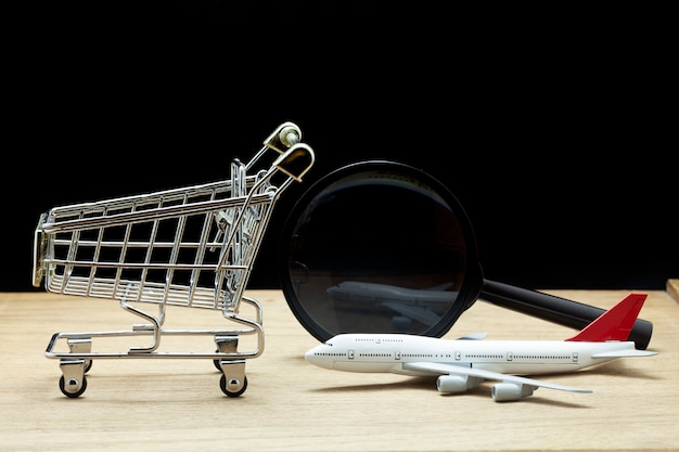 Airplane model with shopping cart and magnifying glass on wood,black background