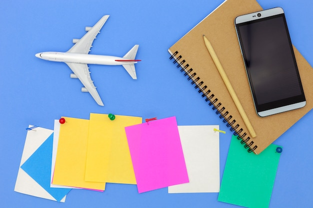 Airplane model with smartphone and paper note on blue background