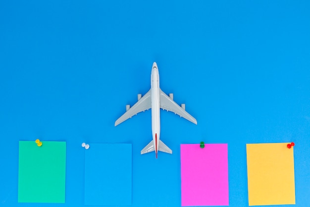 Airplane model with stick paper note on blue background with copy space