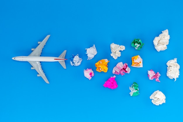 Airplane model with various paper ball on blue background with copy space