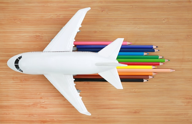 Airplane model on wooden background with colored pencil to concept speed of jet aircraft.