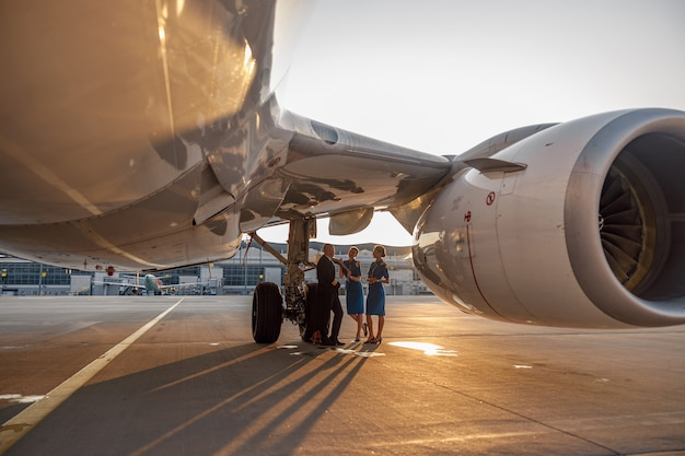Airplane near the terminal in an airport at the sunset. pilot and two stewardesses standing together and talking after landing or before departure. aircraft, aircrew, occupation concept