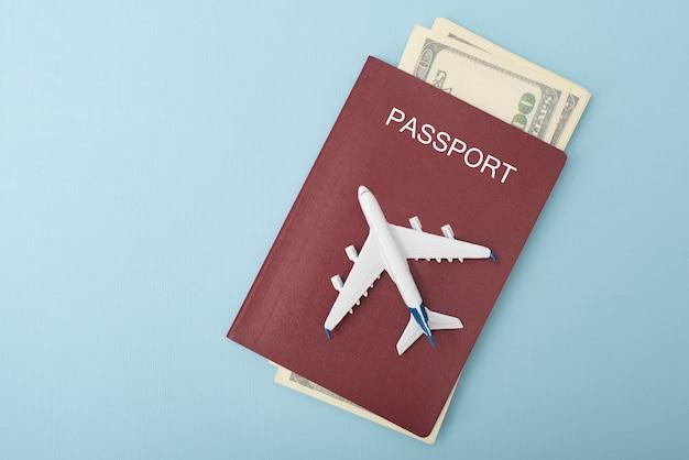 パスポートの表紙にある飛行機。ドル。旅行のコンセプト。青い背景