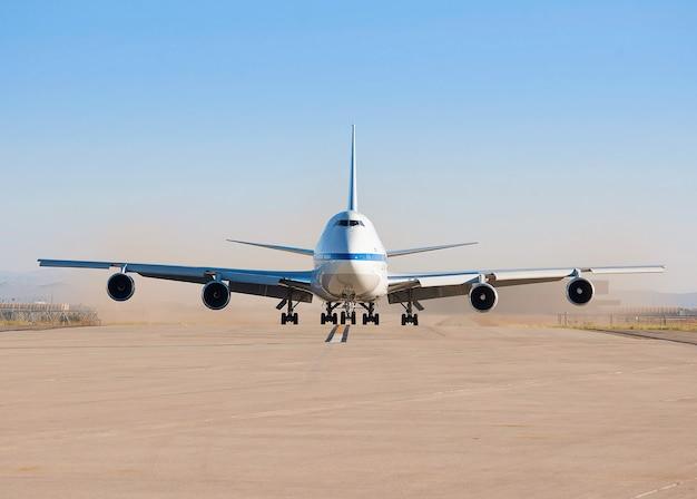 Стоянка самолета на взлетно-посадочной полосе аэропорта в солнечный день
