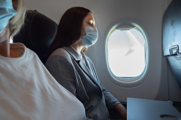 飛行機の乗客は、パンデミックの間、医療用マスクで飛んでいます。旅行のコンセプト。