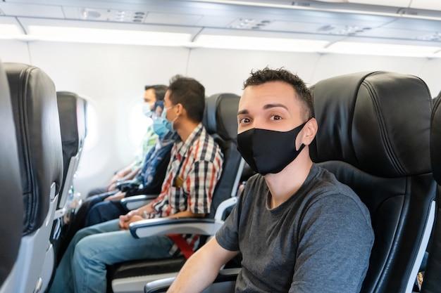 飛行機の乗客は自分の顔に医療用マスクをつけています。コロナウイルスのパンデミック時の空の旅。航空会社の要件。