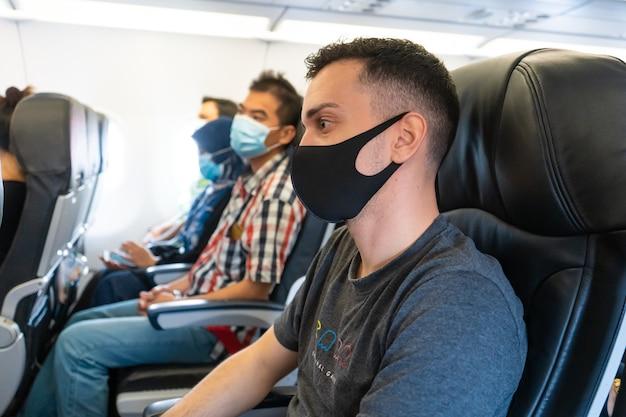 飛行機の乗客は自分の顔に医療マスクを着用しています。コロナウイルスのパンデミック時の空の旅。航空会社の要件。
