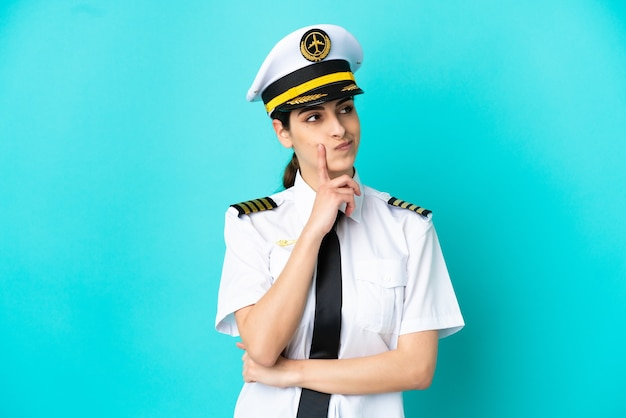Airplane pilot caucasian woman isolated on blue background having doubts while looking up