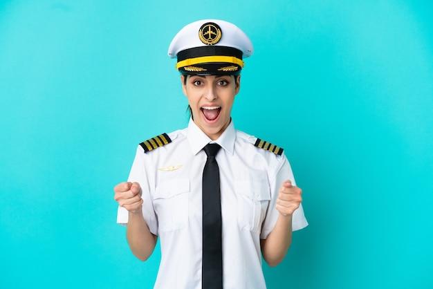 Кавказская женщина пилот самолета изолирована на синем фоне празднует победу в позиции победителя