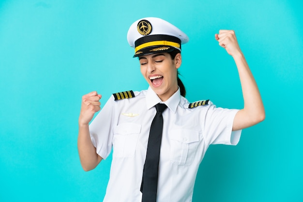 Кавказская женщина пилот самолета изолирована на синем фоне празднует победу