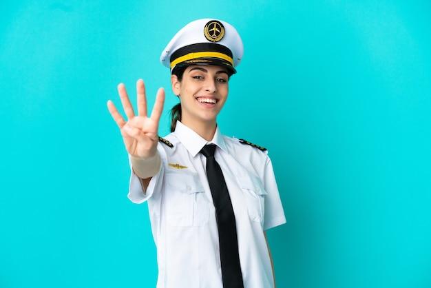파란색 배경에 고립 된 비행기 조종사 백인 여성이 행복하고 손가락으로 4를 세고 있습니다.