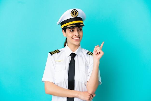 Кавказская женщина пилот самолета изолирована на синем фоне, указывая вверх отличную идею