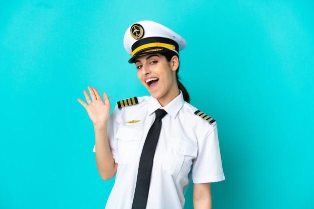 Кавказская женщина пилота самолета изолирована на синем фоне, салютуя рукой с счастливым выражением лица