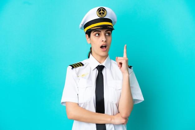 Кавказская женщина пилот самолета изолирована на синем фоне, думая, что идея указывает пальцем вверх