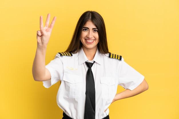 노란색 배경에 격리된 비행기 조종사는 행복하고 손가락으로 세 개를 세고 있습니다.