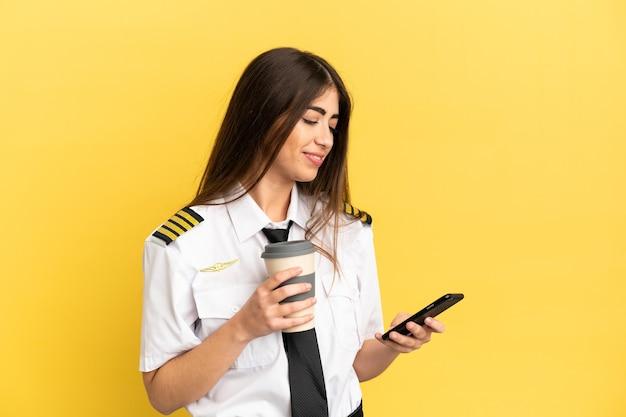 Пилот самолета изолирован на желтом фоне, держа кофе на вынос и мобильный
