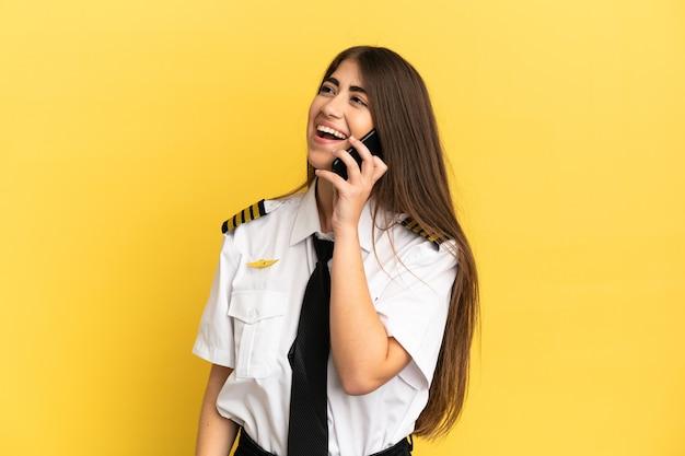 Пилот самолета, изолированные на желтом фоне, разговаривает по мобильному телефону