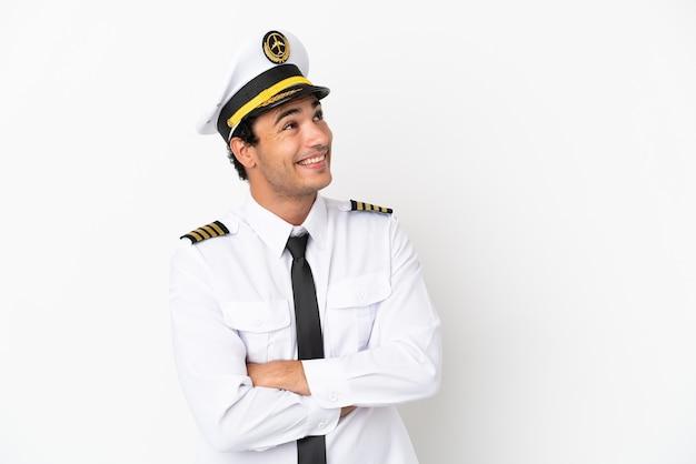 笑顔で見上げる孤立した白い背景の上の飛行機のパイロット