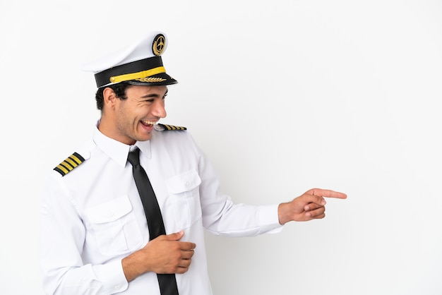 孤立した白い背景の上の飛行機のパイロットは、指を横に向けて製品を提示します