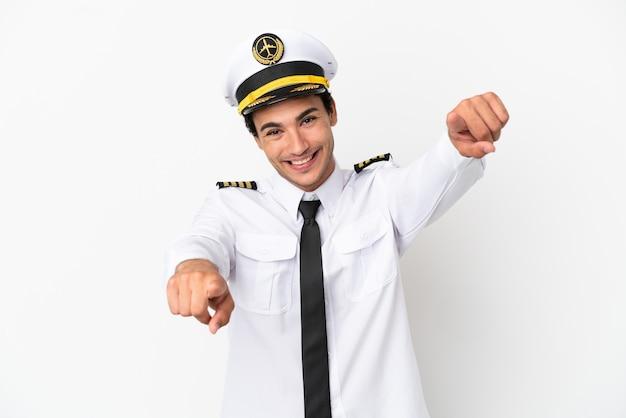 孤立した白い背景の上の飛行機のパイロットは笑顔であなたに指を指しています