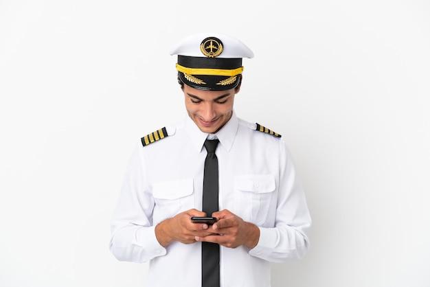 Пилот самолета на изолированном белом фоне, отправив сообщение с мобильного телефона