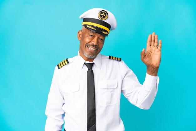 Airplane pilot senior man isolated on blue background saluting with hand with happy expression