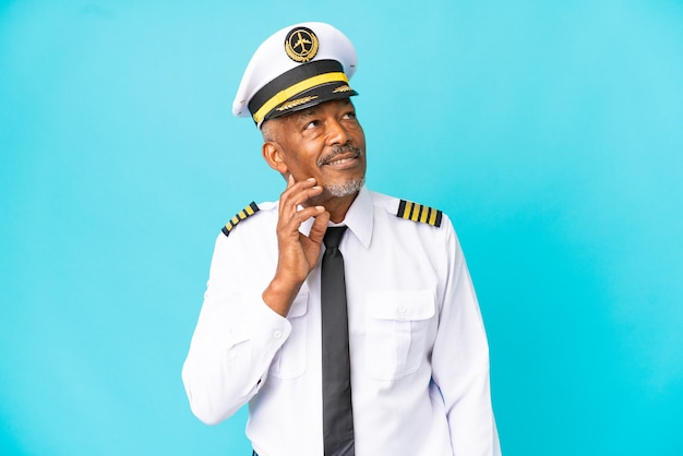 Airplane pilot senior man isolated on blue background thinking an idea while looking up