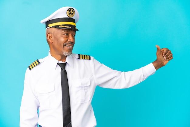 제스처를 엄지손가락을 포기 하는 파란색 배경에 고립 된 비행기 조종사 수석 남자