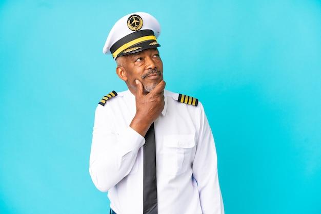 Старший мужчина пилот самолета изолирован на синем фоне, сомневаясь