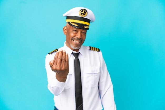 Человек пилот самолета старший, изолированные на синем фоне, приглашая прийти с рукой. счастлив что ты пришел