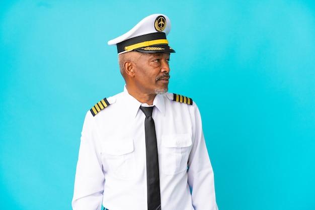 Старший мужчина пилот самолета изолирован на синем фоне, глядя в сторону