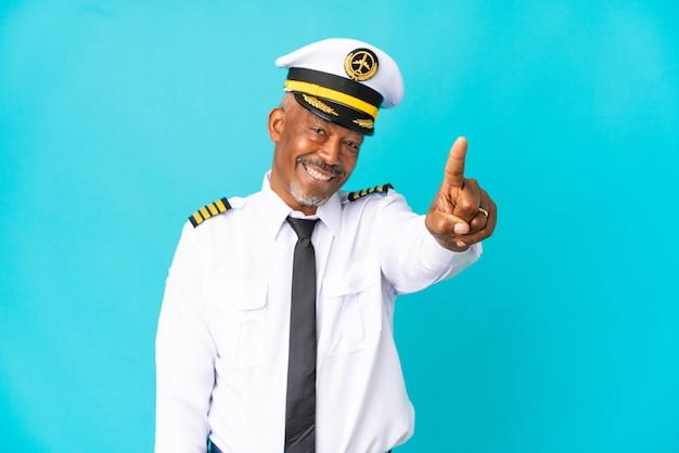 파란색 배경에 고립 된 비행기 조종사 시니어 남자가 손가락을 보여주고 들어 올립니다.