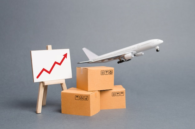 Airplane plane takes off behind stack of cardboard boxes and stand with red up arrow
