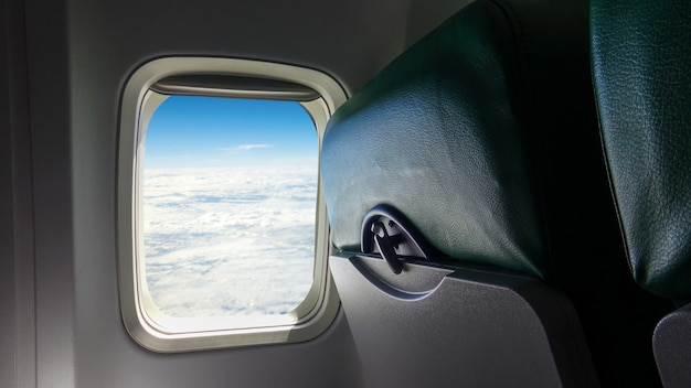 Airplane seat and windows inside an aircraft. view on blue sky and clouds from airplane passenger window. beautiful white cloud as seen through window of a plane. traveling concept.