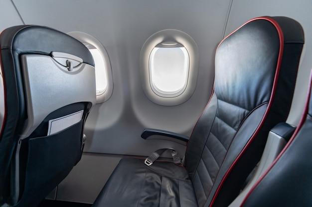 飛行機の座席と窓。乗客なしのエコノミークラスの快適な座席。新しい低コスト航空会社