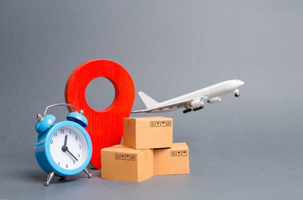 Airplane and stack of cardboard boxes, red position pin and blue alarm clock