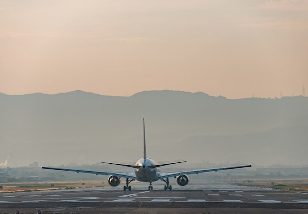 Airplane standing on the airport runway at evening.