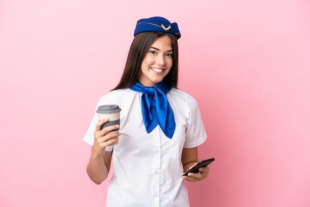 Стюардесса самолета бразильская женщина изолирована на розовом фоне держит кофе на вынос и мобильный