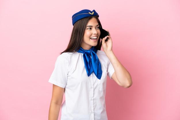 비행기 스튜어디스 브라질 여성은 분홍색 배경에 격리되어 휴대전화와 대화를 나눴습니다.