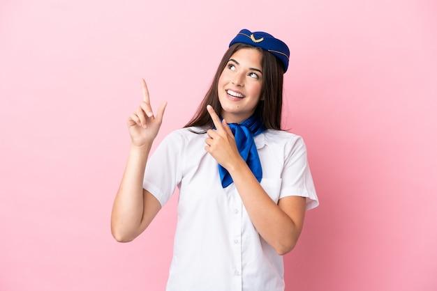 Бразильская женщина-стюардесса изолирована на розовом фоне, указывая указательным пальцем - отличная идея